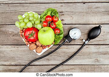 top view of fresh various vegetables, fruits and blood pressure gauge on wooden surface, healthy eating concept