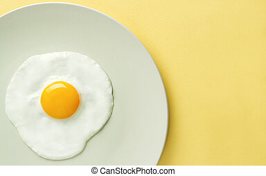 Top view of fried egg on yellow background