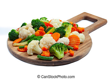 Top view of frozen mixed vegetables cauliflower, carrots, broccoli, sliced bell peppers lying on wooden cutting board