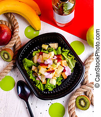 top view of fruit salad with kiwi apple and bananas in a delivery box