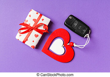 Top view of gift box, car key and wooden heart on colorful background. Luxury present for Valentine's day