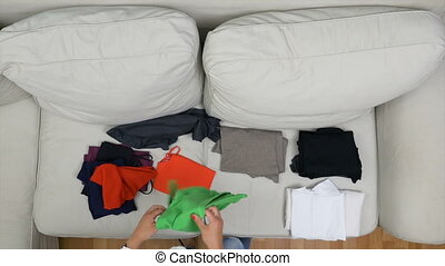 Top view of girl choosing and folding clothes ready for summer holiday