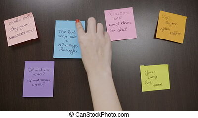 Top view of girl hands adding to handwritten sticky post it...