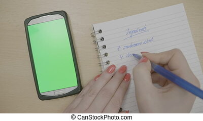 Top view of girl hands with red nails planning to cook dinner writing down recipe ingredients on her agenda while looking at smartphone with green screen