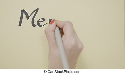 Top view of girl hands writing merry Christmas on a blank...