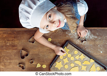 top view of girl with raw shaped cookies on baking tray and cookie cutters on wooden table