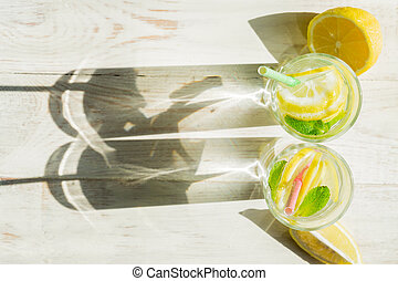 top view of glass of homemade lemonade with lemons, mint and paper straws on wooden rustic background. Summer refreshing beverage. hard shadows
