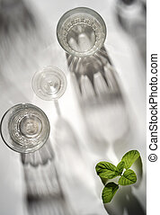 Top view of glasses on white table with mint leaves