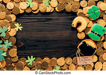 top view of golden coins and icing cookies on table, st patricks day concept