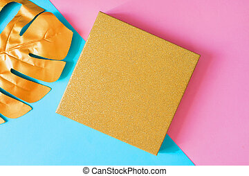 Top view of golden gift box and monstera leaf on double pink and blue background. Minimal flat lay, creative backdrop with copy space