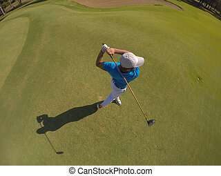top view of golf player hitting shot with club on course at...