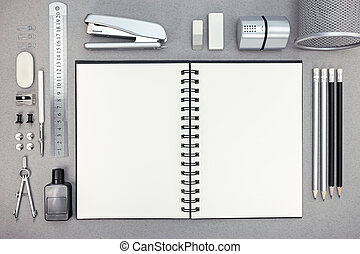 top view of gray workplace with blank notebook and drawing tools