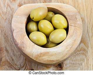 top view of green olives in wooden bowl on plate