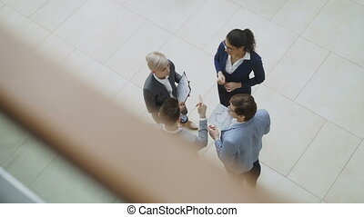 Top view of group of business people in suits discussing...