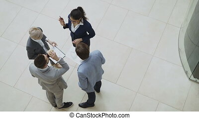 Top view of group of business people in suits discussing financial graphs in lobby of business center indoors
