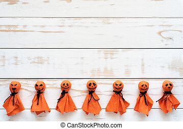 Top view of Halloween crafts, orange paper ghost on white wooden background with copy space for text. halloween concept.