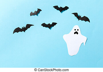 Top view of Halloween crafts, paper ghost on blue paper background with copy space for text. halloween concept.
