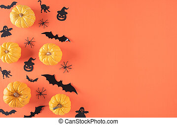 Top view of Halloween crafts, yellow pumpkin, ghost, bat and spider on orange background with copy space for text. halloween concept.