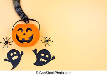 Top view of Halloween decoration, A tail of cat grab jack o lantern, ghost and spider on yellow background with copy space for text. halloween concept.
