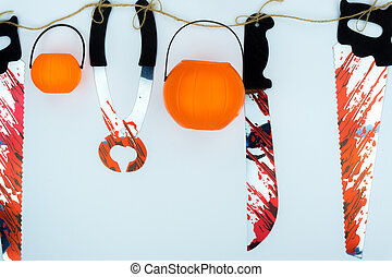 Top view of Halloween decoration, jack o lantern, and bloodstain on the knife and saw on white background with copy space for text. halloween concept.