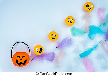 Top view of Halloween decoration, jack o lantern, ghost, bat and colorful feather on white background with copy space for text. halloween concept.