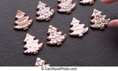 Top view of hand-laid gingerbread cookies (Christmas trees) on a slate table