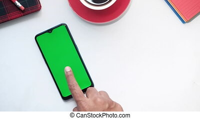 top view of hand using smart phone on white background