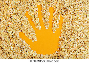 top view of handprint on oat flakes on yellow background