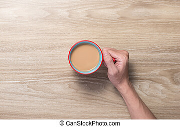 Top view of hands holding a cup of coffee
