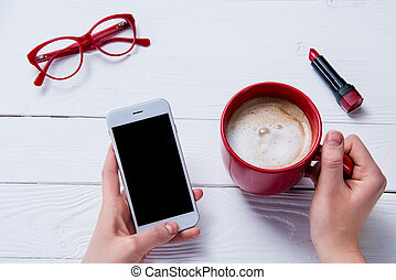 top view of hands holding coffee cup and smartphone with eyeglasses and lipstick on table