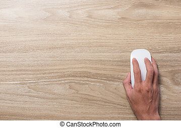 Top view of hands holding mouse on table.