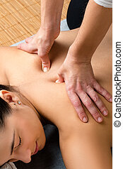 Top view of hands massaging neuro emotional area on upper back.