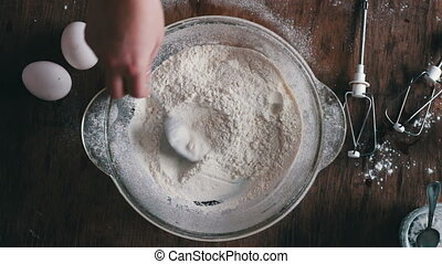 Top view of hands stirred the flour with a spoon.