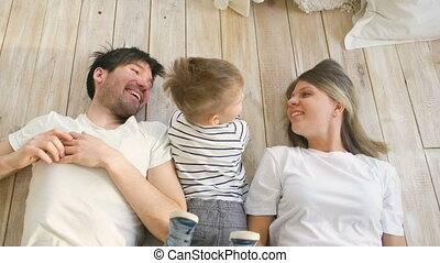 Top view of handsome father and mother play and hug their little son while lying on the floor