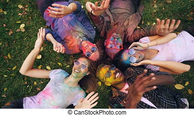 Top view of happy friends male and female lying on grass in park with faces and clothing covered with bright paint, looking at camera and moving hands, smiling.
