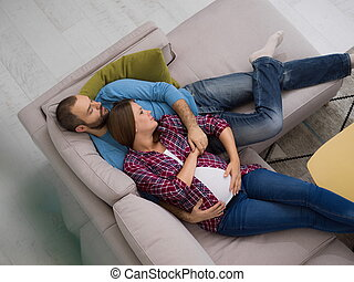 pregnant couple relaxing on sofa