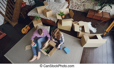 Top view of happy young couple unpacking things, opening box, taking things and talking after moving to new apartment. Relationship and relocation concept.