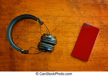 Top view of headphones and smartphone on wooden table.