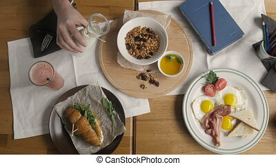 Top View of Healthy Breakfast in Cafe.Man Pouring Milk in Granola, English breakfast: fried egg, bacon toast on a plate, Croissant with Salmon in Modern Cafe