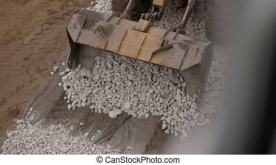 Top view of heavy duty bulldozer moving gravel on...
