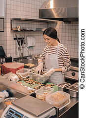 Top view of helpful waitress helping in the kitchen cutting food