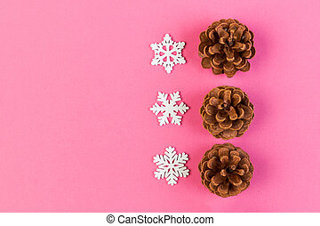 Top view of holiday composition made of pine cones and white snowflakes on colorful background. Winter time and Christmas concept with copy space