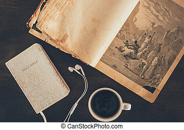 top view of holy bible, earphones and cup on table