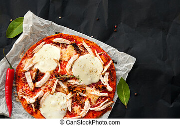 Top view of home made thin fresh italian pizza served on paper and black background