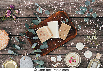 top view of homemade natural soap, eucalyptus, spa treatment and salt on wooden board