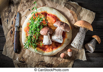 Top view of homemade pizza with mushrooms on baking paper