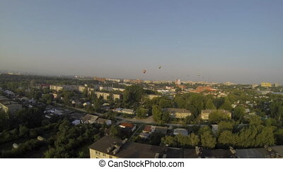 Top view of hot air balloons and city in summer