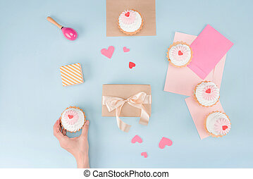top view of human hand holding cake with gift box and blank notes mock-up, birthday party