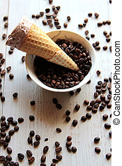 top view of ice cream cone in a bowl filled with coffee beans on white background