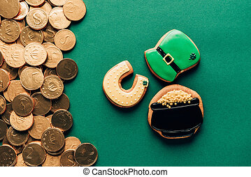 top view of icing cookies and golden coins on green, st patricks day concept